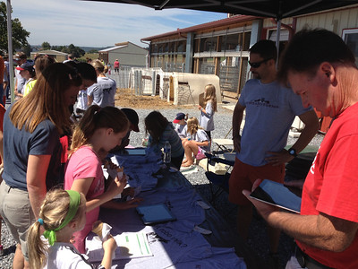 Visitors take a six-question quiz on iPads after touring the facilities at Kurtland Farms' open house Saturday. The quiz entered visitors into a drawing to win free t-shirts.