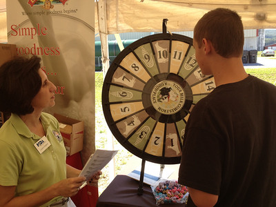 A visitor spins a game wheel at Saturday's open house at Kurtland Farms.