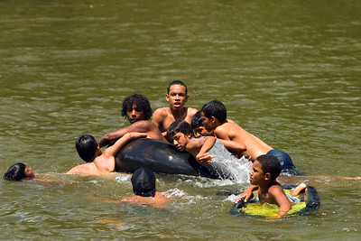 Children playing on inner tube in the Belize River at Boom, Belize District, Belize.