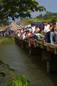 Crowd gathers on the Iguana Creek Bridge on the Belize River to see the La Ruta Maya River Challenge 2008 race go by, Cayo, Belize.