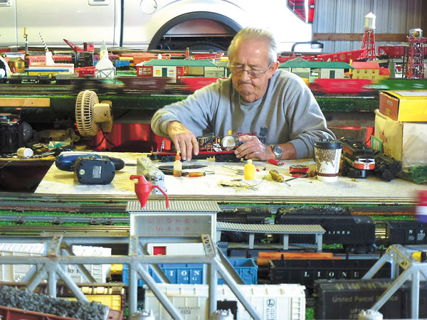 Debbie Wachter/NEWS<br /> Robert G. Frederick, 73, of Washington, Pa., tinkers with a toy train car, one of many he has on display at his model railroad setup at the fair. His collection includes his firs t train set that he got when he was 6. He also has one dating back to 1900. Both of them still run, he said.
