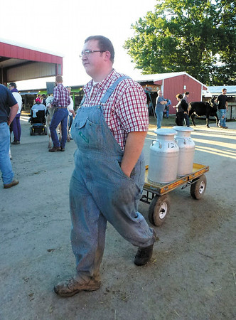 Debbie Wachter/NEWS George Colpetzer, 19, of Greenville, transports whole mlk in traditional milk cans from the milking parlor at the fair.