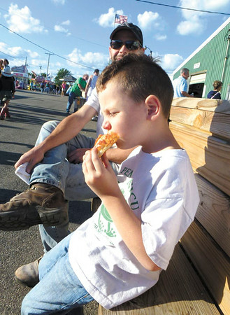 Debbie Wachter/NEWS Archer Brua, 5, of Eastbrook, bites into a slice of pizza on the midway at the fair. His dad is by his side.