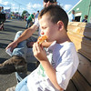 Debbie Wachter/NEWS<br /> Archer Brua, 5, of Eastbrook, bites into a slice of pizza on the midway at the fair. His dad is by his side.