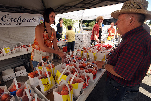 "Bob Biesk, right, buys some Palisade peaches from Shelly Reusch of Tate Orchard.<br /> The annual Lafayette Peach Festival was held downtown on Saturday.<br />  For more photos and a video, go to  <a href=""http://www.dailycamera.com"">http://www.dailycamera.com</a>.<br /> Cliff Grassmick / August 22, 2009"