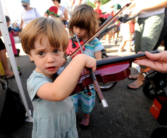 "Sabrina Langer, 3, and her sister Vanessa, 5,  both of Longmont, try to play violin at one of the vender booths on Saturday.<br /> The annual Lafayette Peach Festival was held downtown on Saturday.<br />  For more photos and a video, go to  <a href=""http://www.dailycamera.com"">http://www.dailycamera.com</a>.<br /> Cliff Grassmick / August 22, 2009"