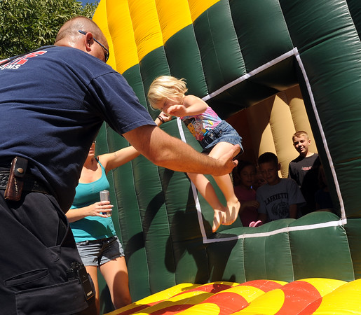 """Ashli Martin of Lafayette jumps out of the Lafayette Fire Safety  House at the festival.<br /> The annual Lafayette Peach Festival was held downtown on Saturday.<br />  For more photos and a video, go to  <a href=""""http://www.dailycamera.com"""">http://www.dailycamera.com</a>.<br /> Cliff Grassmick / August 22, 2009"""