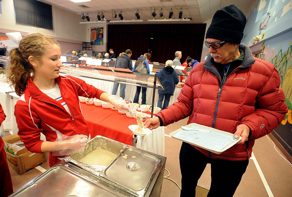 """Sara Keeney, left, of the Centaurus Cheer Squad, serves oatmeal to Kenyon Kugler.<br /> The 14th annual Lafayette Oatmeal Festival was held Saturday. For more photos and a video, go to  <a href=""""http://www.dailycamera.com"""">http://www.dailycamera.com</a>.<br /> Cliff Grassmick / January 8, 2011"""