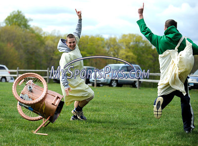 4/28/2010 Mike Orazzi | Staff Southington High School students Jim Hammond (left) and Tim Leahy (right)  take first place in the chariot races during Latin Day at Holiday Hill in Prospect on Wednesday.
