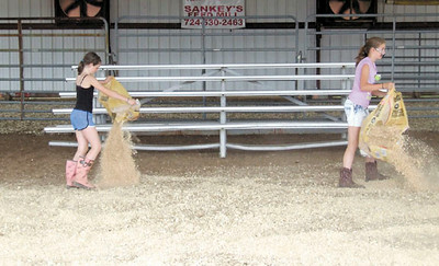 Gary Church/NEWS<br /> Sidney Andrews, 10, left, and Jordan Radzyminski, 10, Spread wood shavings on the floor of the Livestock Area at the Lawrence County Fairgrounds yesterday to prepare for the lamb showmanship program. Both are students in the Mohawk school district.