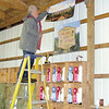 Lenny Stewart, a staff member at the Lawrence County Fair, hangs sign for the wine display yesterday at the fair.