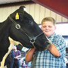 Debbie Wachter/NEWS<br /> Christopher Bozlinski stands in the dairy area with his Holstein cow, Lullabye, during the cheese auction.