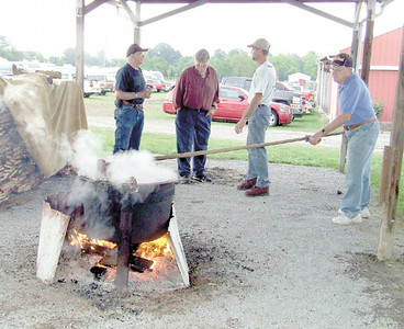 Gary Church/NEWS George Brenneman, stirs apple butter for local Grange organizations at the Lawrence County Fair yesterday, Also shown are from left are, Dave Harvey, John Skiba and Rick Jones.