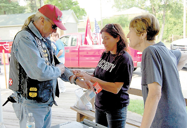 Volunteer Kimberlee Kearcher, an eighth-grade teacher from New Castle Junior High School, registers Jim Shaw and provides him with an arm band for the Fallen Warrior Ride at Cascade Park. Linda Herman, another volunteer, looks on. The Friday event sent more than 100 motorcyclists and emergency vehicles on a one-hour ride to the Lawrence County Fair, where participants then attended the For God and Country Crusade staged by Vision Ministries of Lawrence County. — Samp Luptak Jr.