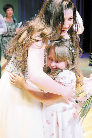 Caroline Orrico gets a hug from her little sister for the event, 6-year-old Victoria Reardon of Hillsville. — Tiffany Wolfe