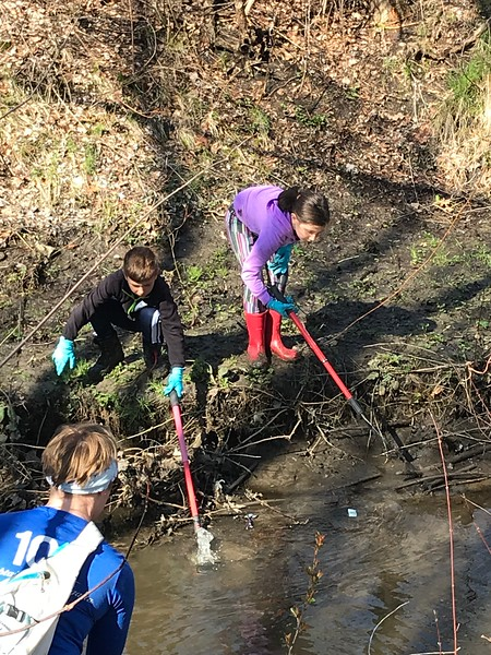 Volunteers in kayaks, canoes, and waders are deployed to remove trash from Broad Meadow Brook.