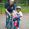 Instructor Rosa Torres lending a helping hand to Christopher Cloud Lee of Coop City during Saturday's Learn to Ride a Bike at Crotona Park.