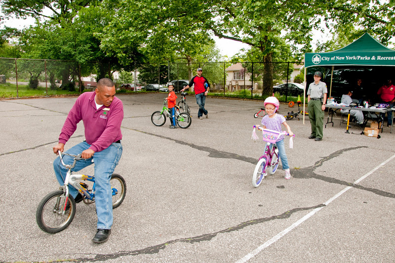 Bronx Boro Events Coordinator and Bike Instructor Gustan O'Neal demonstrate to Camila Peña how first to walk on a bike before she can race around the Crotona Park.  Looking on his Park Ranger Kathy Vazquez, Camila's little brother Becquer on his own bike and their father Socrates.