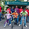 Instructors and students take pause for a photo at Learn to Ride a Bike Day at Crotona Park.  On bicycles are Socrates with his duaghter Camila and son Becquer, Caslyn Gorndon, with Instructors standing from left to right Sonia Honeyghan, Rosa Torres, Gustan O'Neal, Josefina Guzman, Cherlya Shepard and Melvina Lawson.