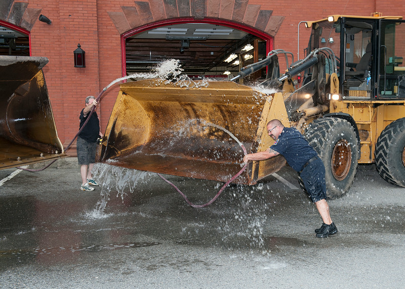 Leominster Fire Department's Alan Averso, left, and Bob Penning, right, have some fun while preparing a set of front loaders for about 1600 galons of ice and water to be poured on members of the Leominster Fire Department for the ALS Challenge on Wednesday.