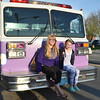 Tiffany Thibodeau, 20, and Skylar Boisvert, 12, pose for a photo with Mayor Dean Mazzarella's purple fire truck. SENTINEL & ENTERPRISE / Ashley Green