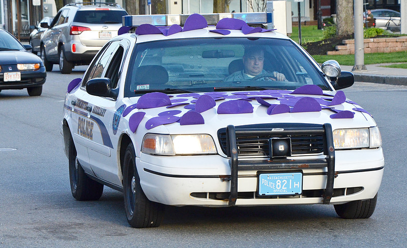 A purple police vehicle escorts Mayor Dean Mazzarella to Leominster City Hall on Thursday evening for the Light the Town Purple event in honor of the upcoming Greater Gardner Relay for Life. SENTINEL & ENTERPRISE / Ashley Green