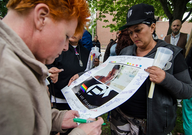 City Councilor Amy Green signs a poster, held by Aida Maldonado, during a vigil in remembrance of the Orlando shooting victims on Monday evening on the Fitchburg Upper Common. Pictured on the poster is former Leominster resident Jeffrey Rodriguez who was wounded in the shooting. SENTINEL & ENTERPRISE / Ashley Green