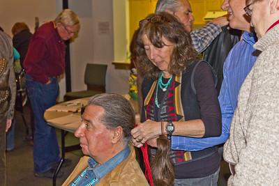 Leon Littlebird getting his hair tied in traditional Navaho ceremonial fashion by Cheri Breeman.