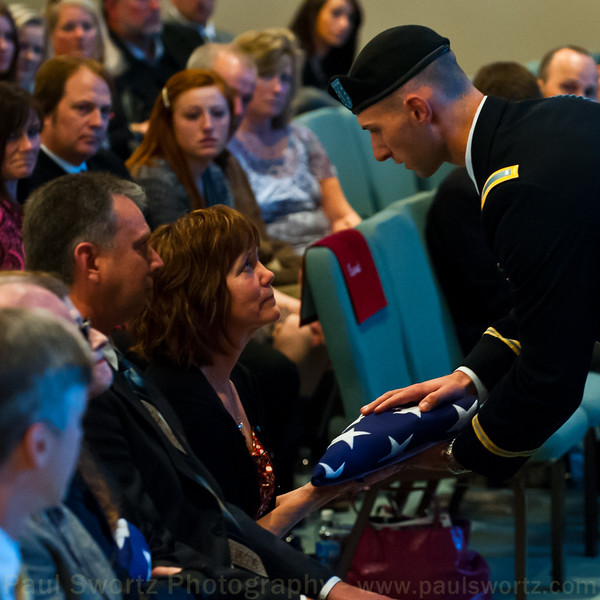 A current soldier from the 506th of the 101st Air Assault gives Tracy Compton a flag that flew over the current Easy Co for 30 days in Afghanistan.