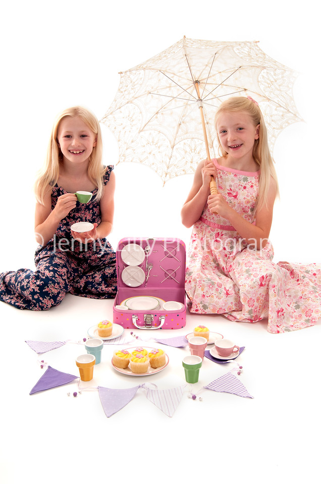 Summer tea party with little girls, childs' tea set, and bunting, isolated on white background