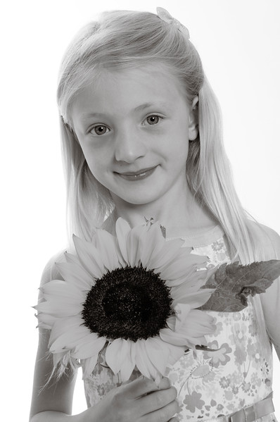 pretty blonde child with sunflower isolated on white background