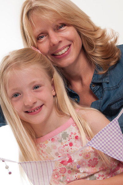 pretty blonde girl and her mother having a cuddle with bunting, isolated on white background