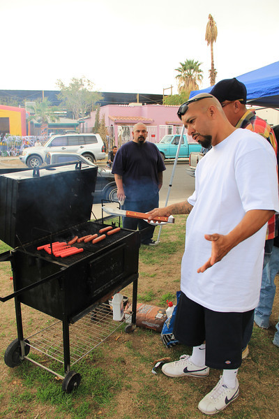 """Meet one of the members from """"Los Malvados"""" bicycle club. For the day's event he cooked hot dogs, hamburgers, and carne asada which a thin slice of steak topped with pico de gallo. The food was plentiful and delicious."""