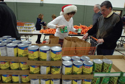 Darien Lions Club Member Joe Marchese and his wife (Womans Club member) Cathy bag food at the Darien Park District to be delivered to needed families Friday Dec. 21, 2012. Erica Benson—ebenson@shawmedia.com