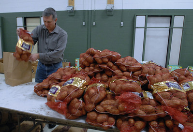 Darien Lions Club Member Jeff Mikula helps bag patatoes at the Darien Park District while him as well as other members and volunteers bag food to be delivered to needed families Friday Dec. 21, 2012. Erica Benson—ebenson@shawmedia.com