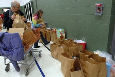 Darien resident Tom Belczak and his daughter Sophia put the bagged food in the Darien Park District gym to be delivered to needed families Friday Dec. 21, 2012. Erica Benson—ebenson@shawmedia.com