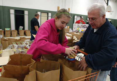 Darien Lions Club Member Ace McDowell and his granddaughter Abby Overmann of Darien bag food at the Darien Park District to be delivered to needed families Friday Dec. 21, 2012. Erica Benson—ebenson@shawmedia.com