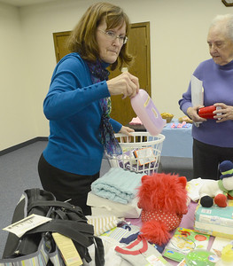 Erica Benson—ebenson@shawmedia.com  Lisle Woman's Club President Lorna Turner as well as other club members provide baby gifts during their baby shower held at the Library Wednesday Feb. 6 2013. The event was held to provide baby gifts for Women's Choice Services in Wheaton.