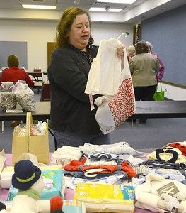 Erica Benson—ebenson@shawmedia.com  Lisle Woman's Club members including Grace  Forker provide baby gifts during their baby shower held at the Library Wednesday Feb. 6 2013. The event was held to provide baby gifts for Women's Choice Services in Wheaton.