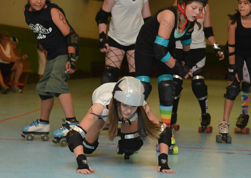 Justin Sheely | The Sheridan Press<br /> A jammer tumbles past the blockers in the level 1&2 match during the Junior Roller Derby mixer at Scotty's Skate Castle Saturday, June 23, 2018. The Bomber Mountain Little Devils team, comprised of competitors from Sheridan, Buffalo and Gillette, hosted teams from Billings for roller derby battle at Scotty's.