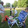 Third Thursday activities at Fay Park in Littleton. Josh Kopelman and his sons Mac, 8, right, and Sam, 10, center, visiting from San Diego, and niece Olivia Kopelman, 8, of Littleton, pick their spot to set up for the movie later. (SUN/Julia Malakie)