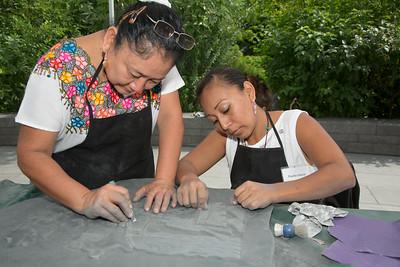 Maria Garcia and Paulita Garcia carve a Mayan Symbol.