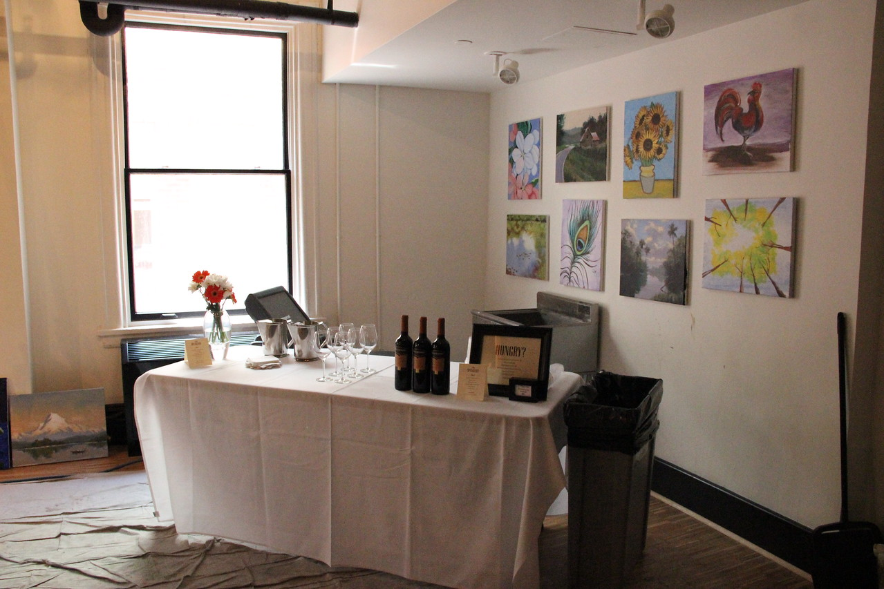 Students sip wine while painting.