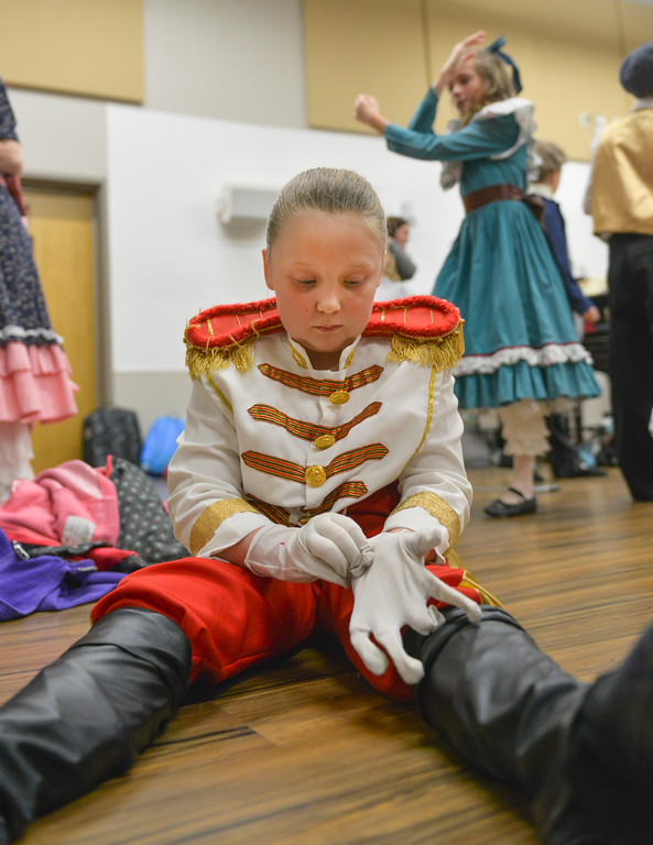 Justin Sheely | The Sheridan Press	<br /> Eight-year-old Lydia Campbell, as a soldier, pulls on a set of gloves in the dressing room during a dress rehearsal of the San Diego Ballet's Nutcracker Tuesday at the Whitney Center for the Arts. Local dance students play roles in the sold-out ballet performances this week.