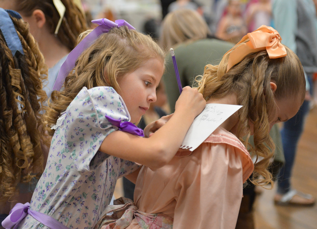 Justin Sheely | The Sheridan Press	<br /> Ten-year-old Josie Yapuncich writes on Isabel Reinke's back in the dressing room during a dress rehearsal of the San Diego Ballet's Nutcracker Tuesday at the Whitney Center for the Arts. Local dance students play roles in the sold-out ballet performances this week.