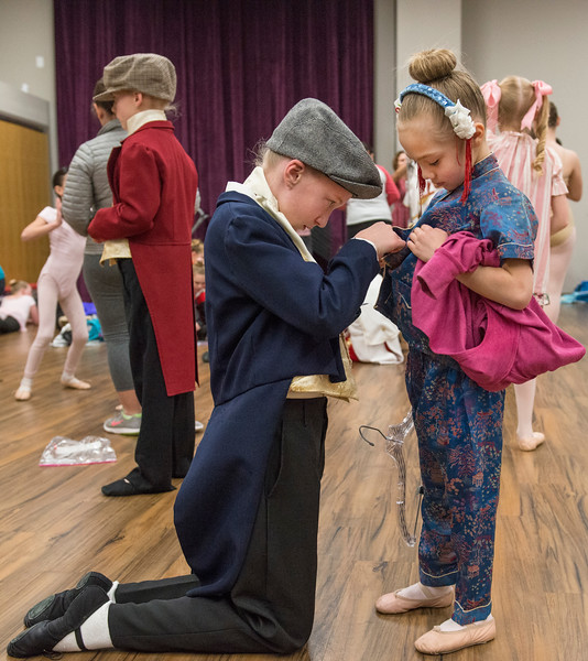Justin Sheely | The Sheridan Press	<br /> Local dance students Ten-year-old Savanah Sutton, left, helps Holly Biteman, 6, with a button in the dressing room during a dress rehearsal of the San Diego Ballet's Nutcracker Tuesday at the Whitney Center for the Arts. Local dance students play roles in the sold-out ballet performances this week.