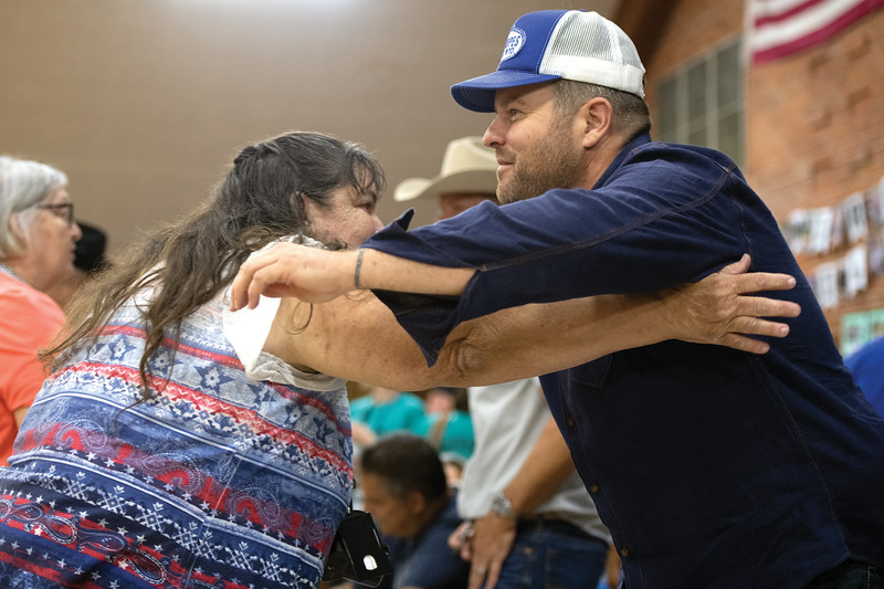 Matthew Gaston | The Sheridan Press<br>Longmire star Adam Bartley reaches across the table to hug fan Donna Wilder during Longmire Days at the Bomber Mountain Civic Center in Buffalo Friday, July 19, 2019.