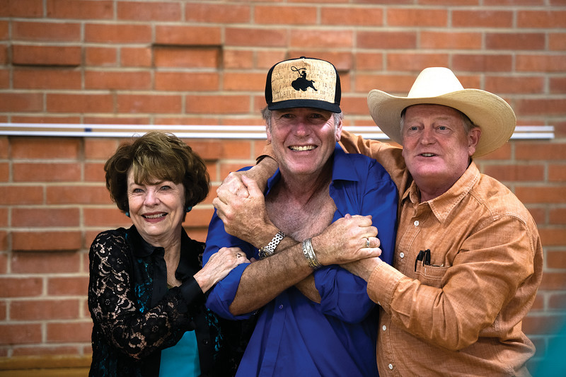 Matthew Gaston | The Sheridan Press<br>Actress Louanne Stephens, left, and writer Craig Johnson, right, razz Longmire star Robert Taylor upon his arrival at the Bomber Mountain Civic Center for an autograph signing Friday, July 19, 2019.