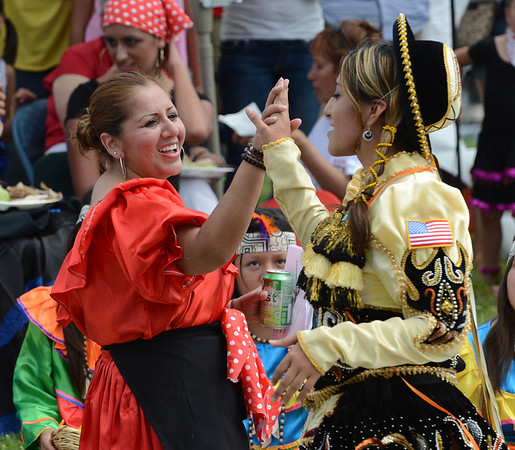 "Elizabeth Torrez, left, gives Roxana Carmen a high five after Carmen's dance performance.<br /> Hundreds of people gathered at Sandstone Ranch in Longmont on Sunday to celebrate the culture of Peru.<br /> For more photos and a video, go to  <a href=""http://www.timescall.com"">http://www.timescall.com</a> or  <a href=""http://www.dailycamera.com"">http://www.dailycamera.com</a>.<br /> Cliff Grassmick  / July 29, 2012"