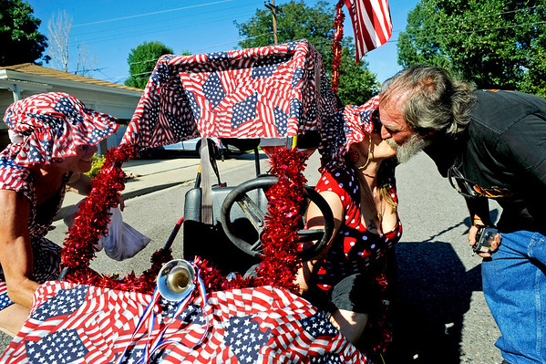 "Merry Vickery (right), of Brighton, kisses her husband Kenny Rayburn while Gwyn Finch readies their float during the Louisville Labor Day Parade in downtown Louisville, Monday, Sept. 7, 2009. The annual event hosted a pie baking contest, food and craft booths, and live music.<br /> DAILY CAMERA/Kasia Broussalian<br /> For more photos and a video of the event, please visit  <a href=""http://www.dailycamera.com"">http://www.dailycamera.com</a>"